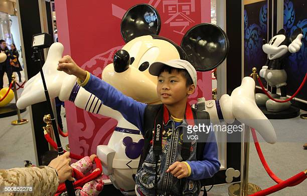 A kid poses with Mickey Mouse displayed at CapitaMall 1818 on December 5 2015 in Wuhan Hubei Province of China Disney Characters exhibition was held...
