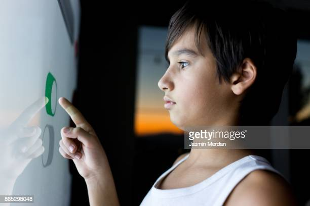 Kid pressing digital button on large smart screen
