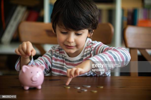 kid put coin to piggy bank - pig stock photos and pictures