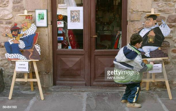A kid puts a letter in the 'Olentzero' mail box next to The Three Wise Men mail box 22 December 2005 in the northern Spanish village of Santesteban...