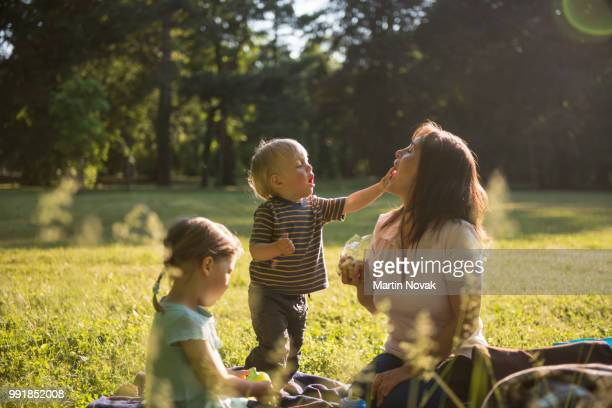 kid putting jelly in mother's mouth - picknick stock-fotos und bilder