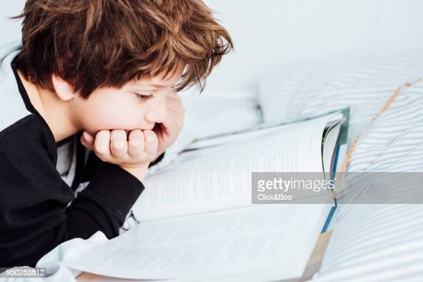 Kid reading a book in bed