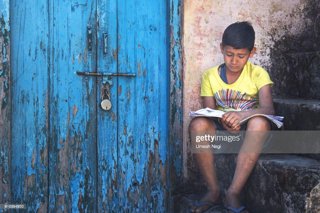 kid reading near locked door : Stock Photo