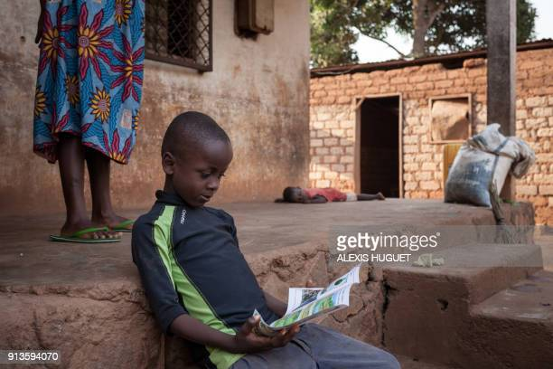 TOPSHOT A kid reads a leaflet distributed by the NGO DanChurchAid to raise awareness about explosives in the Fatima 1 neighbourhood in the 3rd...
