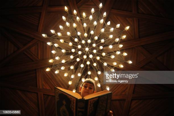 A kid reads Quran during a religious ceremony within the celebrations for Mawlid alNabi the birth anniversary of Muslims' beloved Prophet Mohammad in...