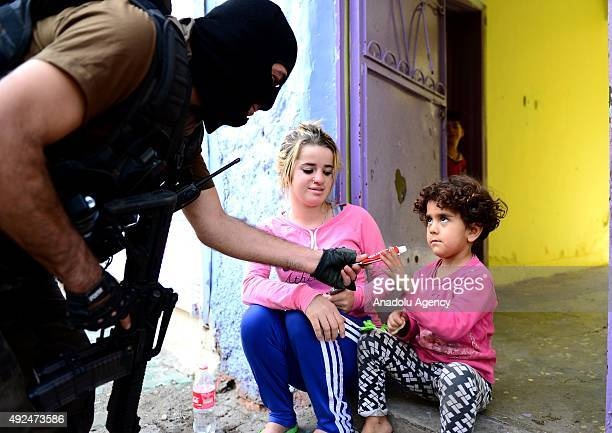 A kid receives a chocolate bar from a member of the Turkish Special Operation team during an operation against terrorist organization PKK in the Sur...