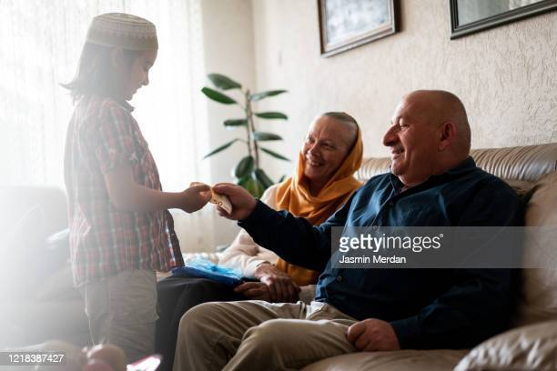 kid receiving money gift from grandparents in eid - eid al adha stock pictures, royalty-free photos & images