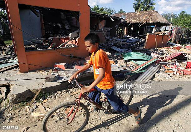 A kid rides a bike amidst the remains of a house after an attack by leftist guerrilla Revolutionary Armed Forces of Colombia 02 November in...