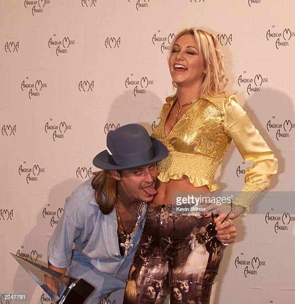 Kid Rock kiddingly licks the stomach of his date backstage at the 28th Annual American Music Awards at the Shrine Auditorium in Los Angeles Monday...