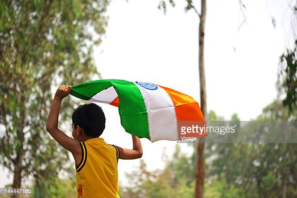 a kid running ,holding the tri-colour flag above his head - indian flag stock pictures, royalty-free photos & images