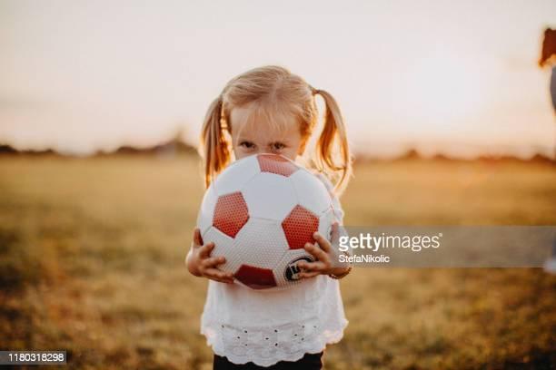 kind läuft mit ball auf wiese - spielball stock-fotos und bilder