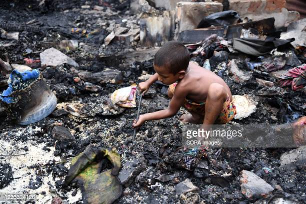 Kid searches for reusable materials after a fire swept through the slum. Several hundreds of houses were gutted as the devastating fire that broke...