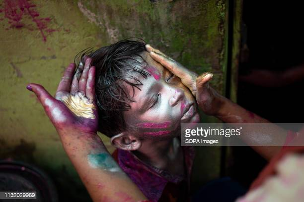 A kid seen getting his face painted the celebration Holi known as the festival of colour is an ancient Hindu spring festival which is now celebrated...