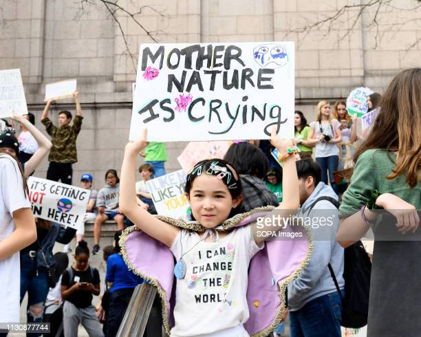 Kid seen holding a placard saying, mother nature is crying, during the Youth Climate Strike protest at the American Museum of Natural History in New...