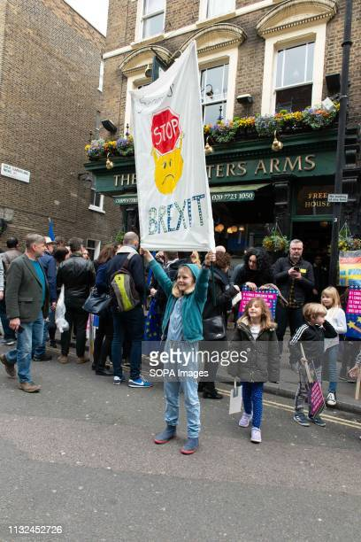 A kid seen holding onto a hanging anti Brexit banner during the protest Over one million protesters gathered at the People's Rally in London...