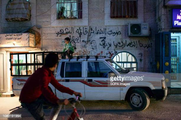 A kid seen seated on top a car parked on the street of the Dheisheh Refugee Camp with martyr graffiti in the background