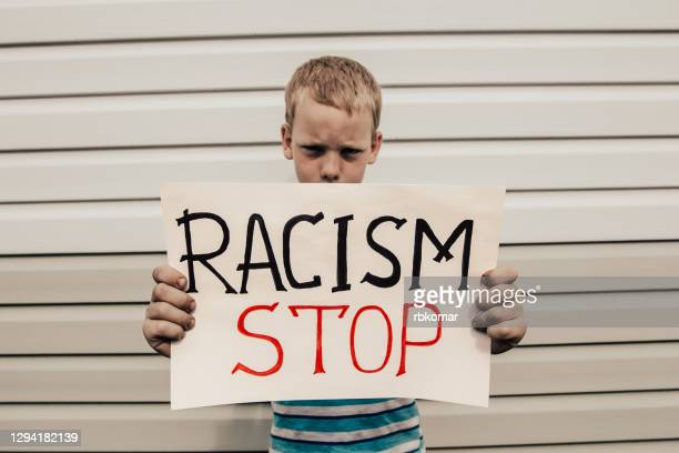 kid shows a poster with the inscription stop racism - black power movement stock pictures, royalty-free photos & images