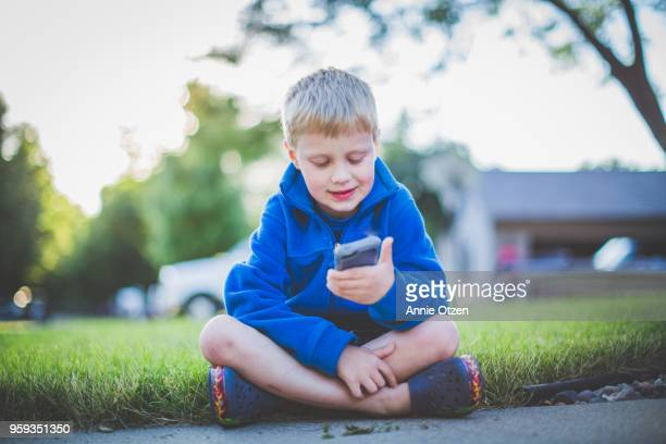 Kid sitting and looking at a cellphone
