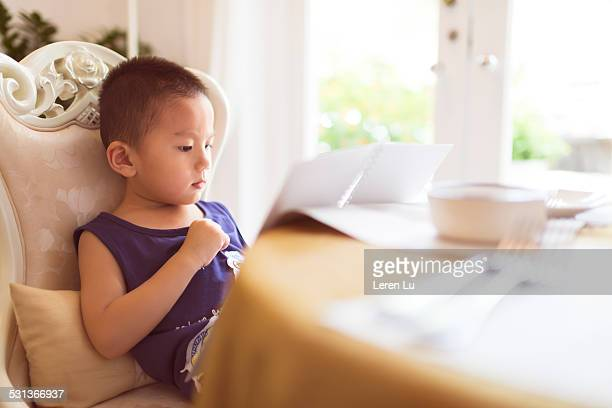 Kid sitting and reading in restaurant