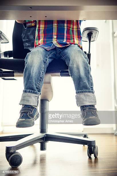 Kid Sitting at Grown-ups Office Desk, View of Feet