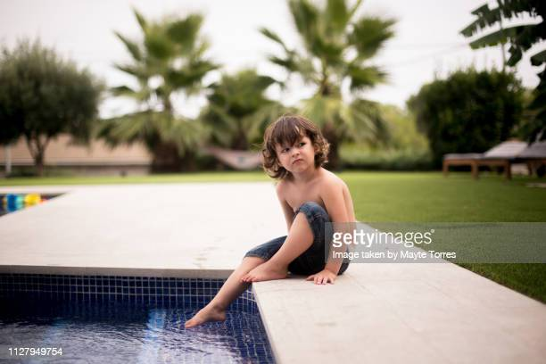 kid sitting at the edge of the pool looking serious - autism awareness stock pictures, royalty-free photos & images