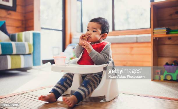 Kid sitting in lounge and eating lunch.