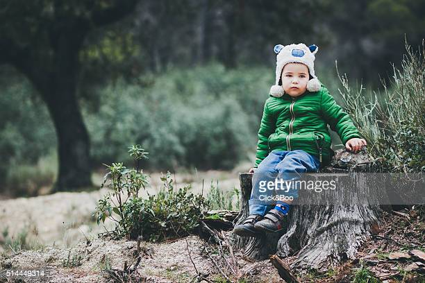 Kid sitting on a tree trunk on the forest