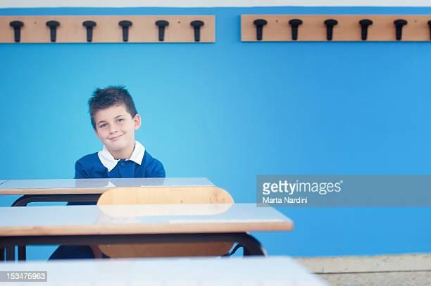 Kid sitting on desk in classroom
