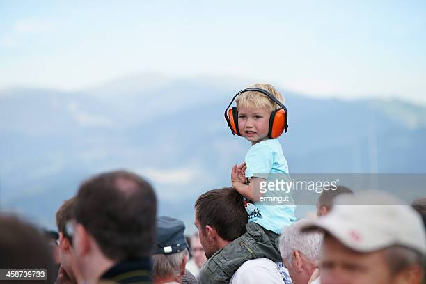 Kid sitting on father's shoulders wearing protective headset
