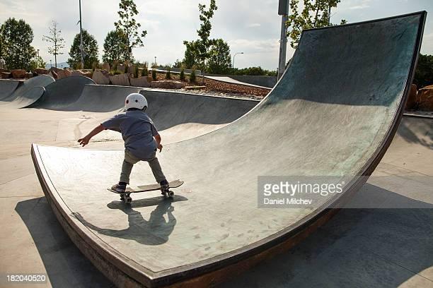 Kid skateboarding at a skate park.