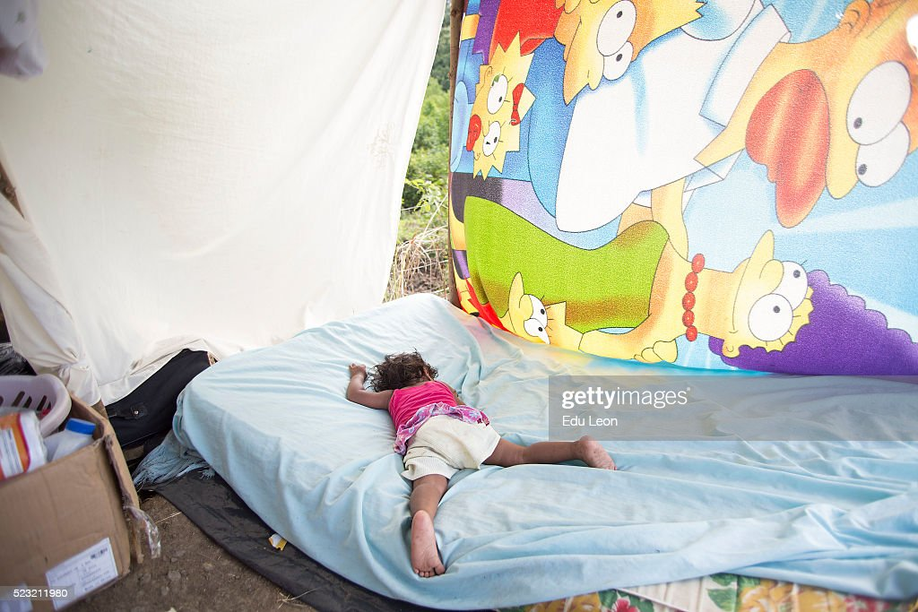 A kid sleeps next to the highway after an earthquake struck Ecuador on April 21, 2016 in Manabi, Ecuador. Some neighbours wait next to the highway to ask people for food. At least 400 people were killed after a 7.8-magnitude quake and the government's food supply is not reaching everyone.
