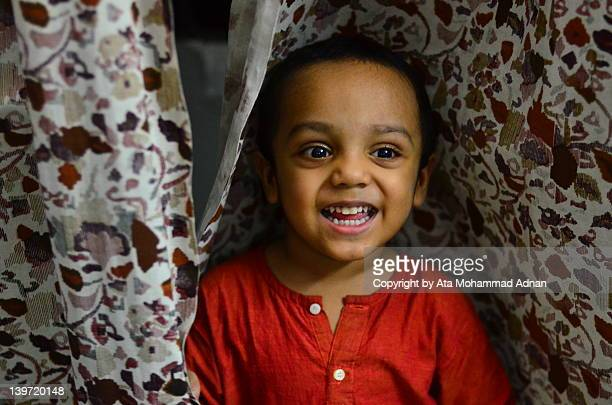 Kid smiling between curtains