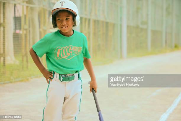 kid (6-7) smiling with baseball bat on field - baseball uniform stock pictures, royalty-free photos & images
