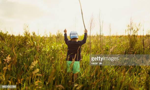 Kid standing in middle of grassy field with stick in his hand.