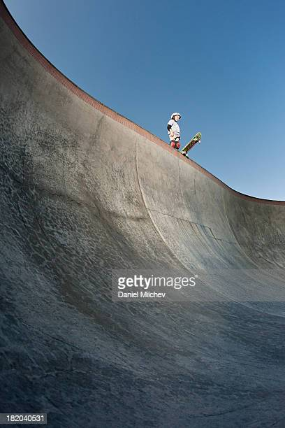 Kid standing on the edge of a skate park bowl.