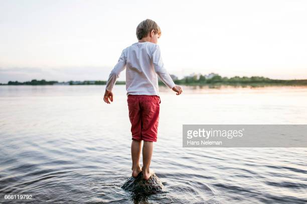 Kid standing on the rock in a river