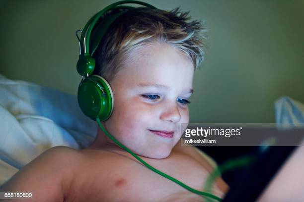 Kid streams movie on tablet and listens to the content with headphones