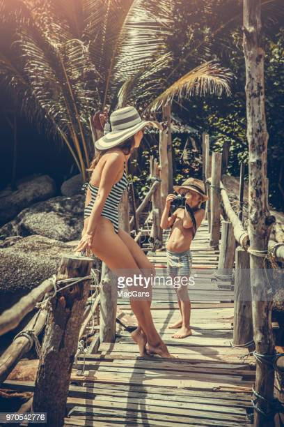kid taking photo of his mother - beach photos stock photos and pictures