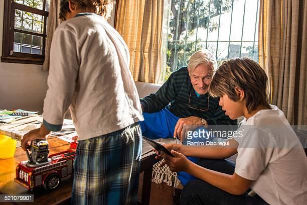Kid Teaching his grandpa the electronic toy