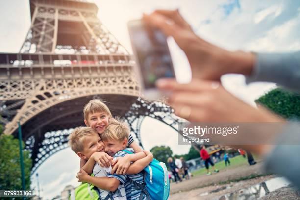 パリ、フランスのエッフェル塔の前で抱きしめる子供観光客