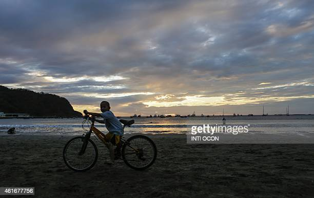 A kid tries to ride a bicycle on the beach of San Juan del Sur in Rivas Nicaragua on January 16 2015 AFP PHOTO/Inti OCON