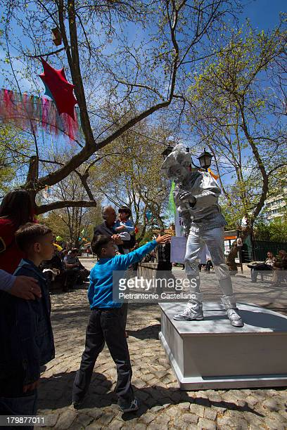 "Kid try to reach for a ""living statue"" artist during the annual Children's Festival in Ankara."