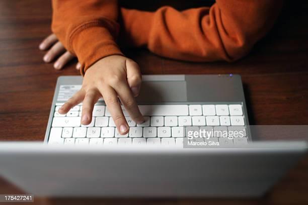 kid typing laptop