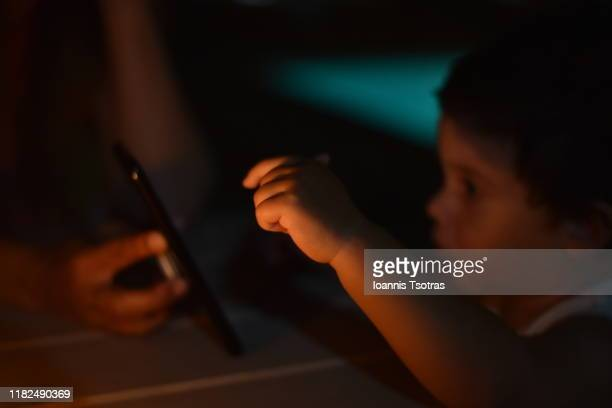 kid using a digital mobile phone tablet in the dark - candle in the dark imagens e fotografias de stock