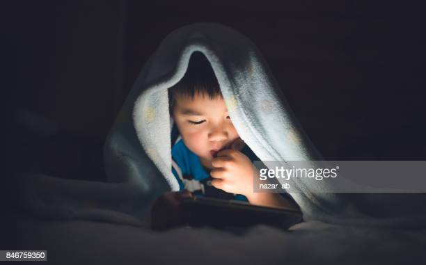 Kid Using Smartphone On Bed.