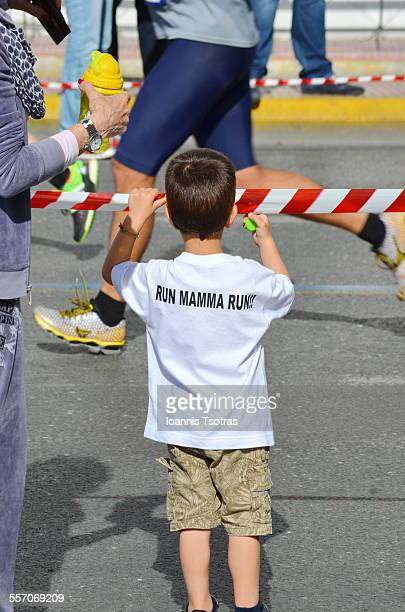 Kid waiting for his Mother during a Marathon