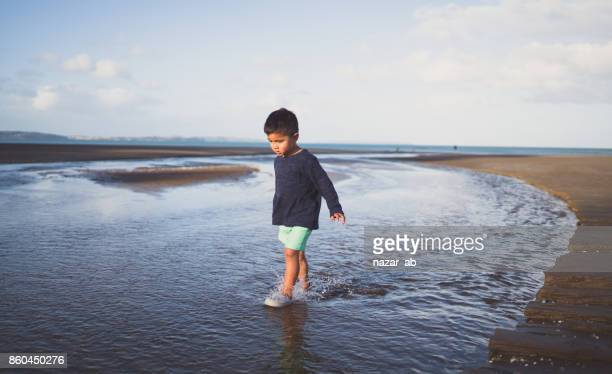 Kid walking in water at long bay, Auckland, New Zealand.