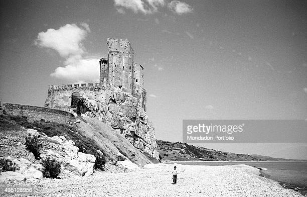 A kid walking on the pebble beach before the Norman fortress named Castrum Petrae Roseti built in the place of an older Basilian monastery the castle...