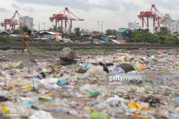 A kid walks on a beach covered with rubbish near slams in Baseco Compound with a view of new skyscrapers in Manila downtown The Batangas Shipping and...