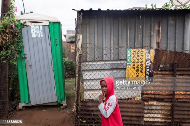 A kid walks past an informal house with a portable toilet and a African National Congress Election Poster wedged in the fence on April 5 2019 in...